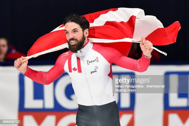 Charles Hamelin of Canada raises the Canadian flag after becoming the overall champion in the men's 3000 meter SuperFinal during the World Short...