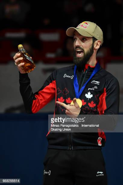 Charles Hamelin of Canada reacts as he holds up a bottle of maple syrup after receiving his gold medal in the men's 1500 meter Final during the World...