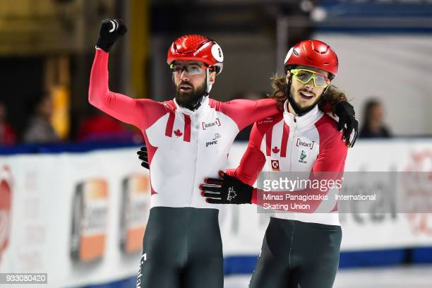 Charles Hamelin of Canada receives a hug by teammate Samuel Girard of Canada after finishing first in the men's 1500 meter finals during the World...
