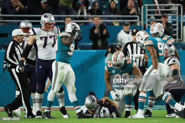 Charles Harris Cameron Wake and Ndamukong Suh of the Miami Dolphins celebrate sacking Tom Brady of the New England Patriots in the fourth quarter at...