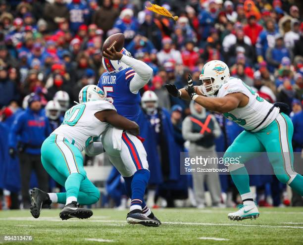Charles Harris of the Miami Dolphins and teammate Ndamukong Suh attempt to tackle Tyrod Taylor of the Buffalo Bills during the first quarter on...