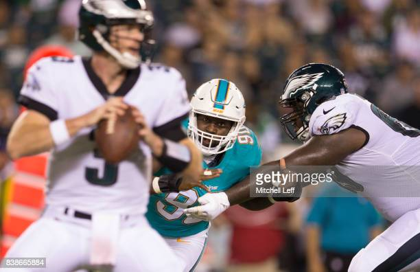 Charles Harris of the Miami Dolphins rushes after Matt McGloin of the Philadelphia Eagles with Dillon Gordon of the Philadelphia Eagles guarding him...