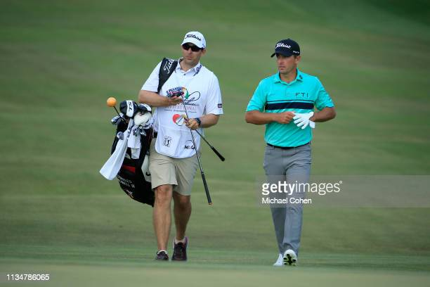 Charles Howell III of the United States walks with caddie Nick Jones after playing a shot on the 15th hole during the third round of the Arnold...