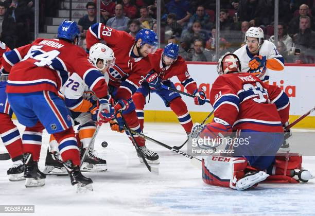 Charles Hudon and Jakub Jerabek of the Montreal Canadiens defends the goal against Anthony Beauvillier of the New York Islanders in the NHL game at...