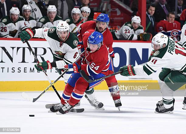 Charles Hudon of the Montreal Canadiens controls the puck against Marco Scandella and Zach Parise of the Minnesota Wild in the NHL game at the Bell...