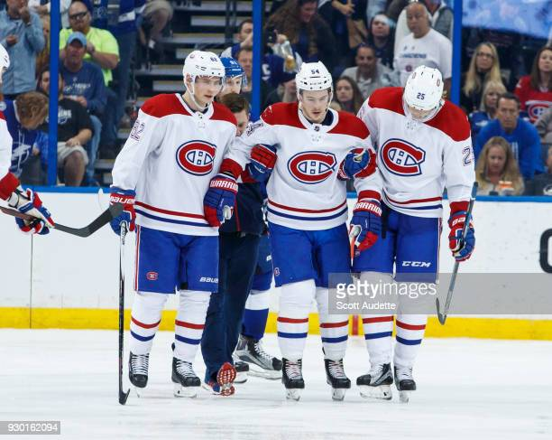 Charles Hudon of the Montreal Canadiens is helped off the ice by teammates Artturi Lehkonen and Jacob de la Rose after being injured against the...