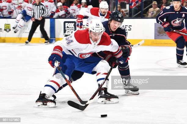 Charles Hudon of the Montreal Canadiens shields the puck from Markus Nutivaara of the Columbus Blue Jackets during the second period of a game on...