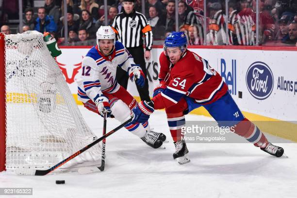Charles Hudon of the Montreal Canadiens skates the puck against Peter Holland of the New York Rangers during the NHL game at the Bell Centre on...