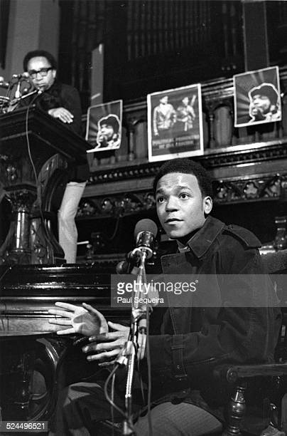 Charles Hurst president of Malcolm X College stands at the podium and listens to Ronald 'Doc' Satchel who survived the police raid that killed Fred...