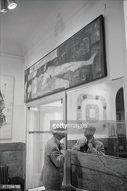 Charles Jackson adjusts his tie in the lobby of New York City's Hotel Chelsea before going out into the street Art work by residents adorns the lobby...