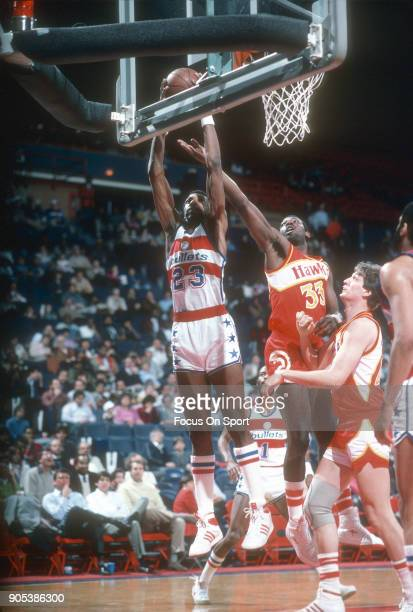 Charles Jones of the Washington Bullets goes up for a rebound over Antoine Carr of the Atlanta Hawks during an NBA basketball game circa 1985 at the...
