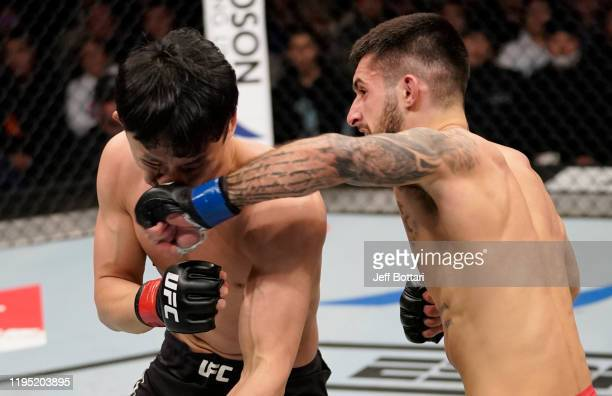 Charles Jourdain of Canada punches Dooho Choi of South Korea in their featherweight fight during the UFC Fight Night event at Sajik Arena 3 on...