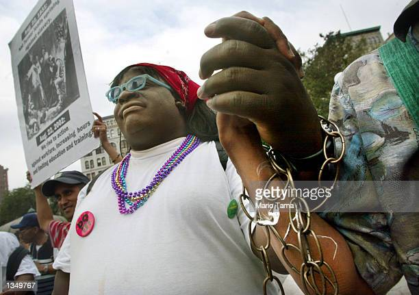 Charles June holds hands with another protester while dressed in chains during a demonstration against welfare reform in Union Square August 22 2002...