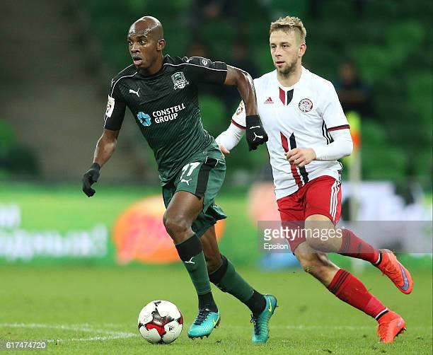 Charles Kabore of FC Krasnodar is challenged by Janusz Gol of FC Amkar Perm during the Russian Premier League match between FC Krasnodar v FC Amkar...
