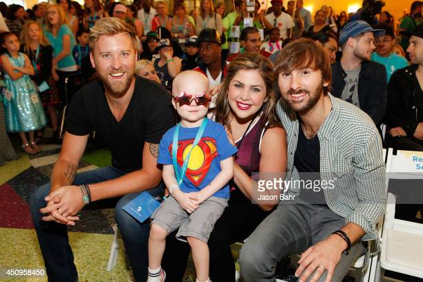 Charles Kelley Hillary Scott and Dave Haywood of Lady Antebellum pose with a patient during the grand opening of Seacrest Studios at Children's...