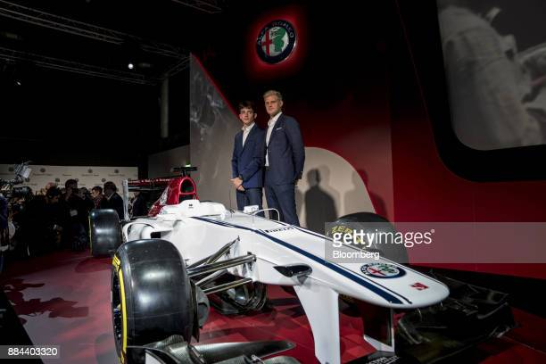 Charles Leclerc left and Marcus Ericsson racing drivers pose for a photograph with the Alfa Romeo Sauber Formula One racing car during a news...