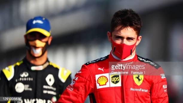 Charles Leclerc of Monaco and Ferrari and Daniel Ricciardo of Australia and Renault Sport F1 stand on the grid prior to the F1 Grand Prix of Abu...