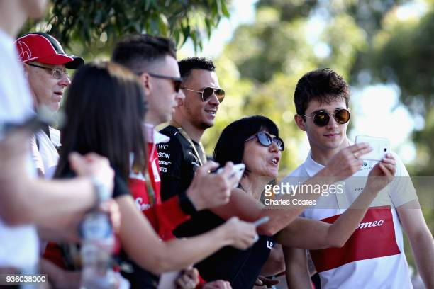 Charles Leclerc of Monaco and Sauber F1 arrives at the circuit and poses for a photo with a fan during previews ahead of the Australian Formula One...