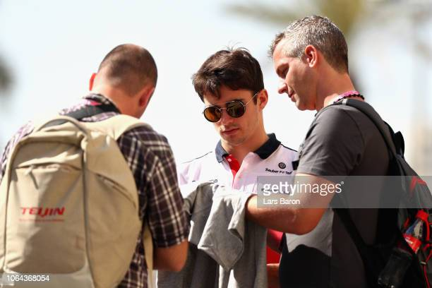 Charles Leclerc of Monaco and Sauber F1 signs autographs for fans before practice for the Abu Dhabi Formula One Grand Prix at Yas Marina Circuit on...