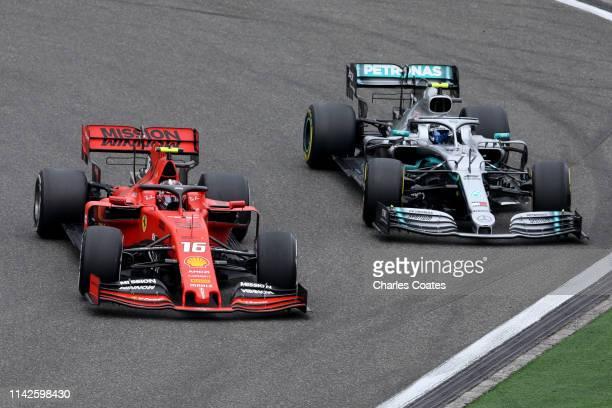 Charles Leclerc of Monaco driving the Scuderia Ferrari SF90 leads Valtteri Bottas driving the Mercedes AMG Petronas F1 Team Mercedes W10 on track...