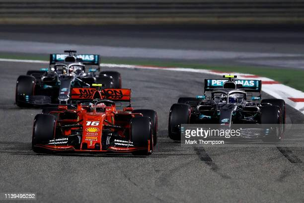 Charles Leclerc of Monaco driving the Scuderia Ferrari SF90 overtakes Valtteri Bottas driving the Mercedes AMG Petronas F1 Team Mercedes W10 on track...
