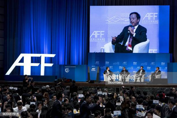 Charles Li chief executive officer of Hong Kong Exchanges and Clearing Ltd right is displayed on a large screen while speaking during a panel...