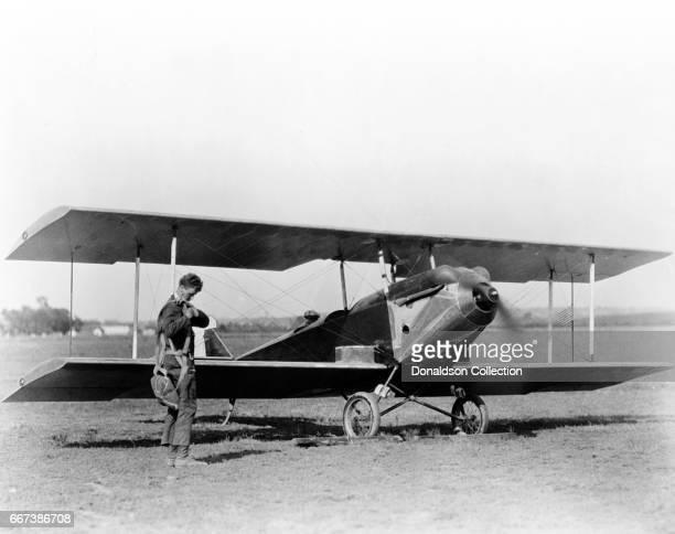 Charles Lindbergh adjusting parachute before testing Sergeant Bell's experimental plane in front of wing of biplane Lambert Field St Louis Missouri...