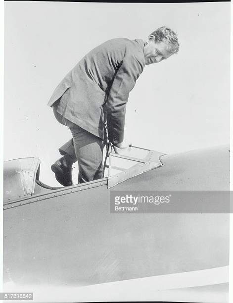 Charles Lindbergh flashing one of those real spontaneous smiles as he steps into the cockpit of the new Lockheed Vega monoplane with retractable...