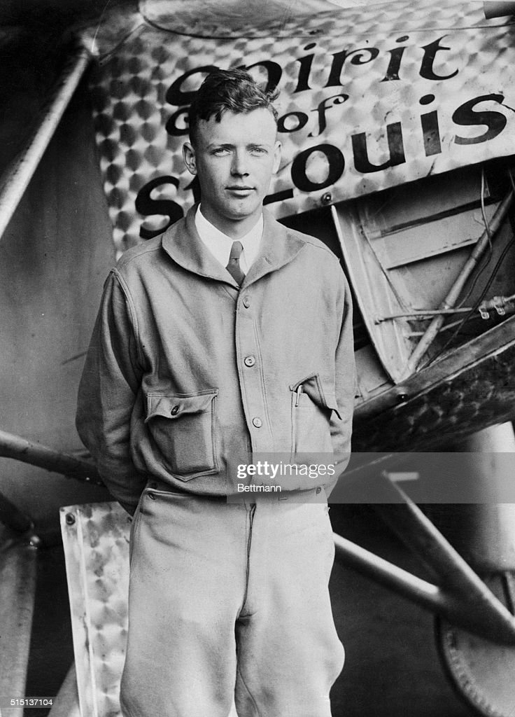 Charles Lindbergh standing in front of the Spirit of St. Louis.