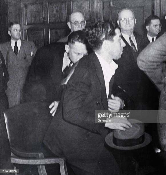 Charles Luciano alleged New York Vice Racketeer was photographed here rising from his chair with two sheriffs standing guard in the rear after...