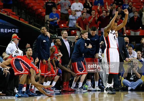 Charles Mann of the Georgia Bulldogs celebrates their 75-73 win as Jarvis Summers and the Mississippi Rebels bench react to a missed field goal by...