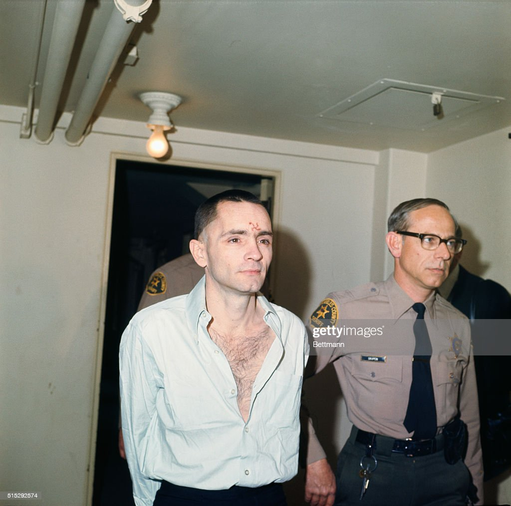 Charles Manson arrives for court with a shorn head, an open shirt, and a swastika carved in his forehead. Manson was convicted for his part in ordering his followers to commit the Tate-LaBianca murders.