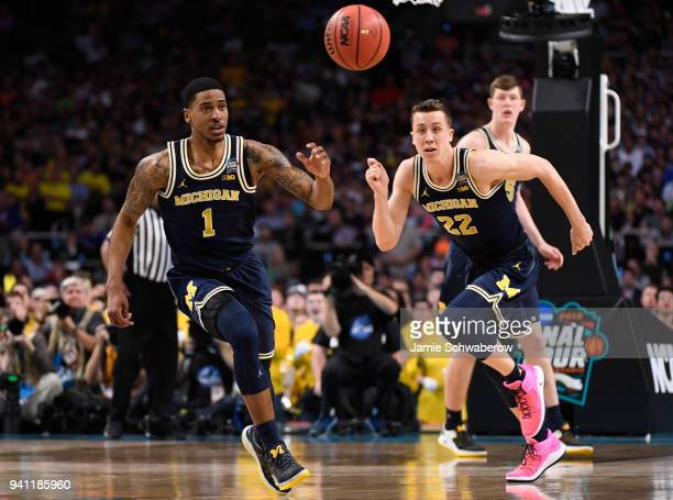 Charles Matthews and Duncan Robinson of the Michigan Wolverines chase after a loose ball during the first half of the 2018 NCAA Photos via Getty...