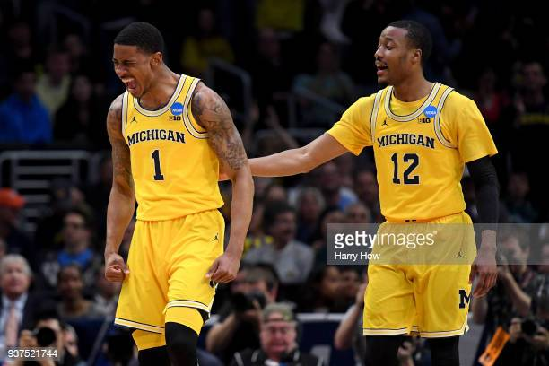 Charles Matthews and MuhammadAli AbdurRahkman of the Michigan Wolverines react after Matthews dunks the ball in the first half against the Florida...