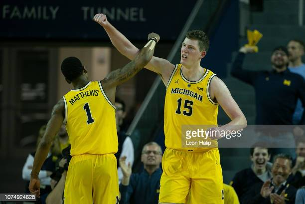 Charles Matthews of the Michigan Wolverines and teammate Jon Teske celebrate a win over the North Carolina Tar Heels at Crisler Center on November 28...
