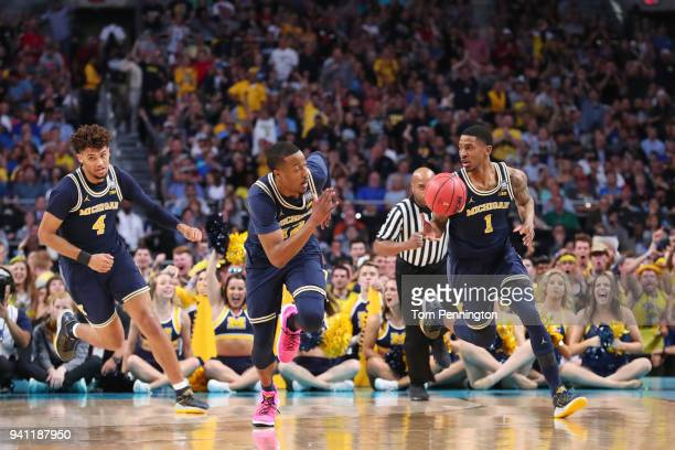 Charles Matthews of the Michigan Wolverines brings the ball up the court with teammates Isaiah Livers and MuhammadAli AbdurRahkman against the...