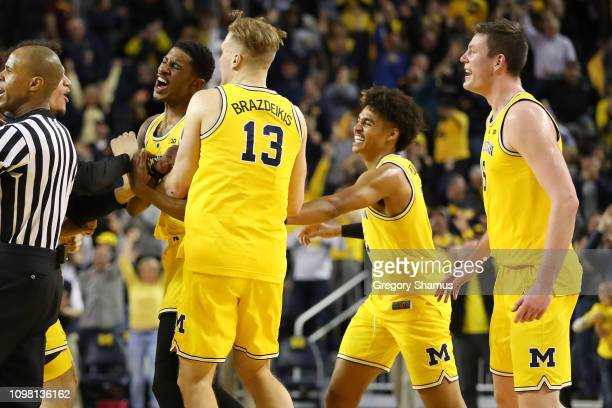 Charles Matthews of the Michigan Wolverines celebrates his buzzer beater game winning shot to beat the Minnesota Golden Gophers 5957 with Ignas...