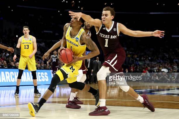 Charles Matthews of the Michigan Wolverines drives on DJ Hogg of the Texas AM Aggies in the second half in the 2018 NCAA Men's Basketball Tournament...