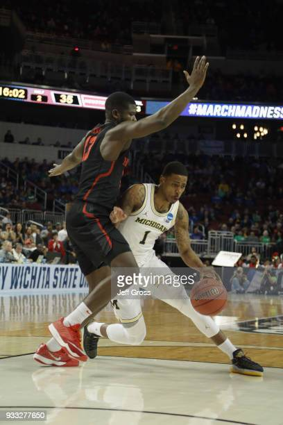 Charles Matthews of the Michigan Wolverines drives on Nura Zanna of the Houston Cougars in the second half during the second round of the 2018 NCAA...