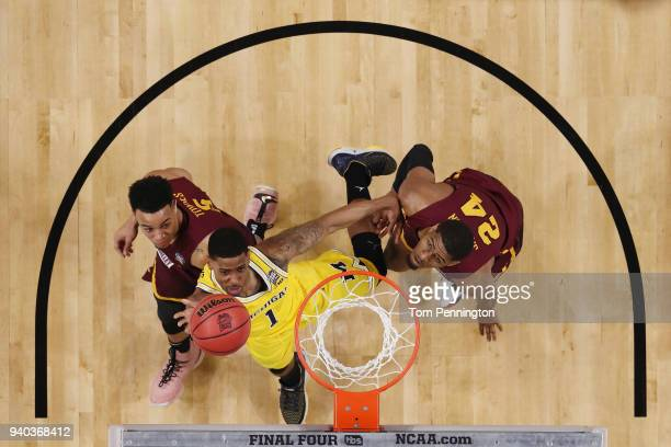 Charles Matthews of the Michigan Wolverines drives to the basket against Marques Townes and Aundre Jackson of the Loyola Ramblers in the first half...