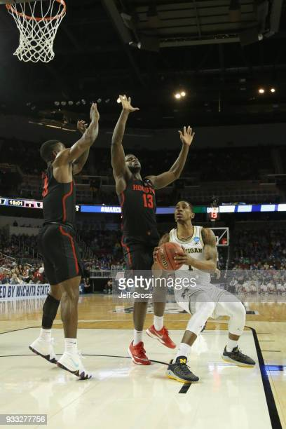 Charles Matthews of the Michigan Wolverines shoots against Nura Zanna and Corey Davis Jr #5 of the Houston Cougars in the second half during the...