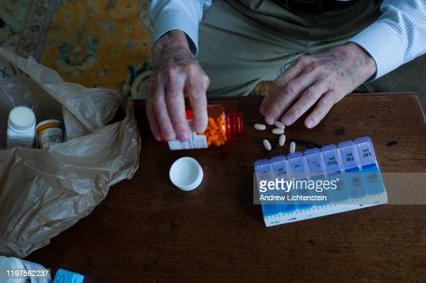 Charles Miller prepares the daily pills his wife will need for the week on January 4 2020 in Sarasota Florida His wife has had a recent stroke and a...