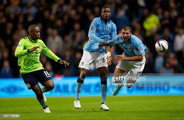 Charles N'Zogbia of Aston Villa is challenged by Abdul Razak of Manchester City and his teammate Aleksander Kolarov during the Capital One Cup match...