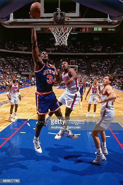 Charles Oakley of the New York Knicks drives to the basket and shoots the ball against the New Jersey Nets at Brendan Byrne Arena in East Rutherford...