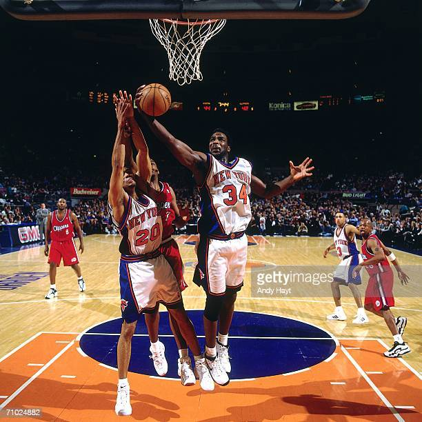 Charles Oakley of the New York Knicks grabs a rebound in the lane against Lamond Murray of the Los Angeles Clippers during a game at Madison Square...