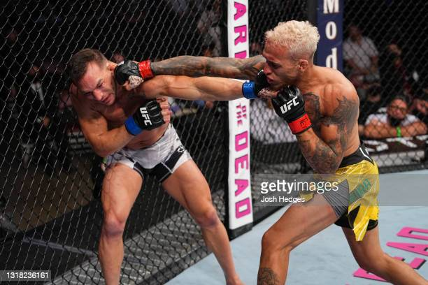 Charles Oliveira of Brazil punches Michael Chandler in their UFC lightweight championship bout at Toyota Center on May 15, 2021 in Houston, Texas.