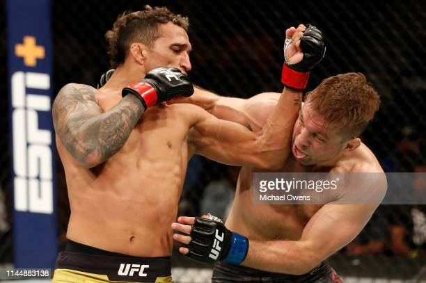 Charles Oliveira of Brazil punches Nik Lentz in their lightweight bout during the UFC Fight Night event at Blue Cross Arena on May 18 2019 in...