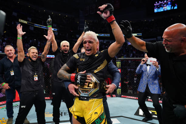 Charles Oliveira of Brazil reacts as UFC President Dana White places the UFC lightweight championship belt around his waist after defeating Michael...