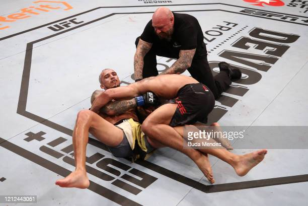 Charles Oliveira of Brazil secures a guillotine choke submission against Kevin Lee in their lightweight fight during the UFC Fight Night event on...