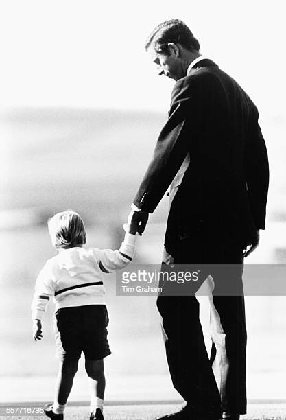 Charles Prince of Wales holding hands with his young son Prince William at Aberdeen Airport Scotland September 7th 1984